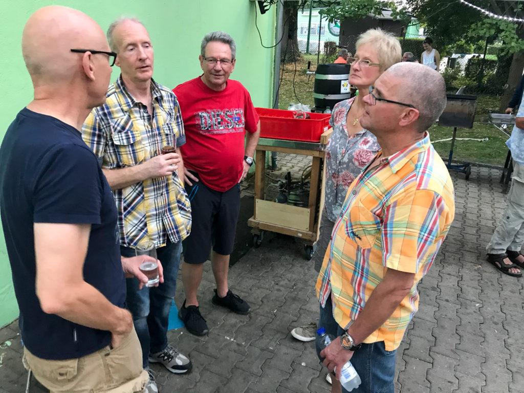 Mitglieder stehen zusammen und feiern